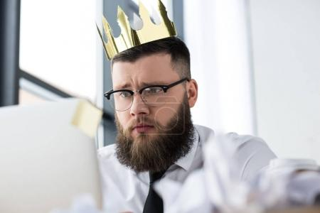 portrait of businessman with paper crown on head working on laptop in office
