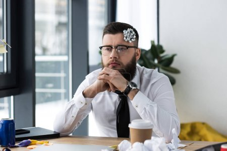 portrait of pensive businessman with bow on head at workplace in office
