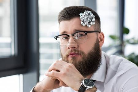 portrait of bearded businessman with bow on head looking at camera in office