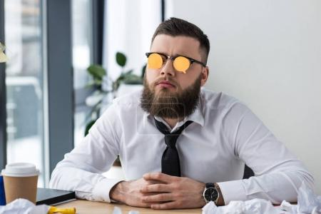 portrait of businessman with sticky notes on eyeglasses at workplace in office