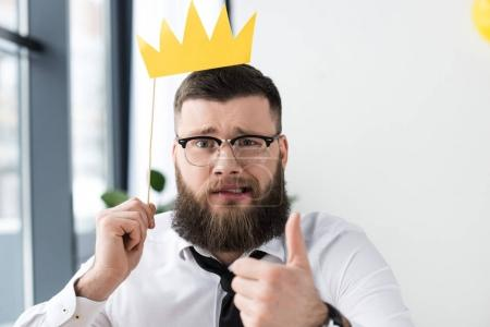 portrait of bearded businessman with paper crown showing thumb up in office
