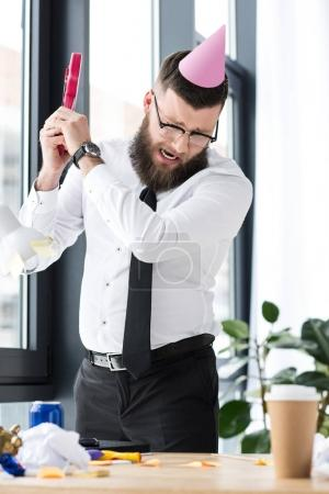 businessman with party cone on head crashing toy guitar in office