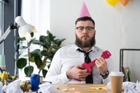 portrait of businessman with party cone on head and toy guitar at workplace in office
