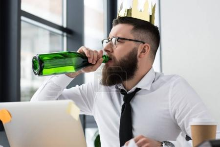 businessman with paper crown on head drinking champagne at workplace in office