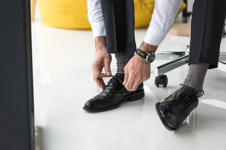 partial view of businessman tying shoelaces in office