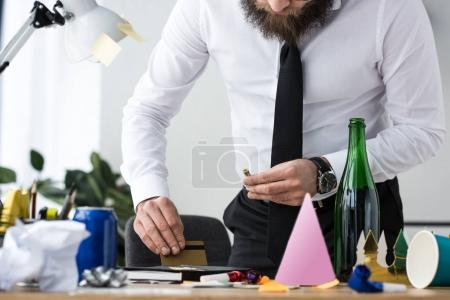 partial view of businessman taking drugs at workplace in office