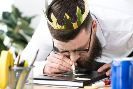 businessman with paper crown on head taking drugs at workplace in office