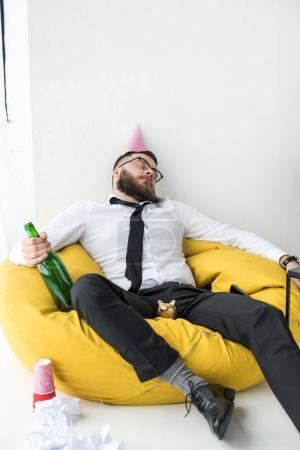drunk businessman in formal wear with paper cone on head sleeping on bag chair