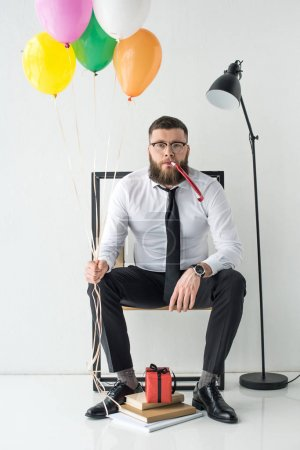 businessman in formal wear with balloons sitting on chair