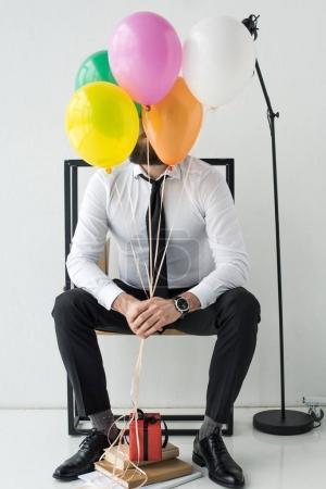Photo pour Obscurci vue d'homme d'affaires avec des ballons colorés, assis sur la chaise - image libre de droit
