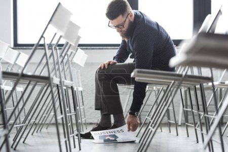 side view of businessman taking newspaper while sitting in meeting room