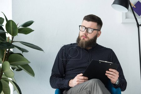 portrait of thoughtful businessman with notepad looking away