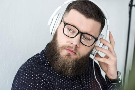 Portrait d'homme barbu songeur en lunettes écouter de la musique dans les écouteurs