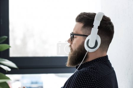 side view of man with eyes closed listening music in headphones