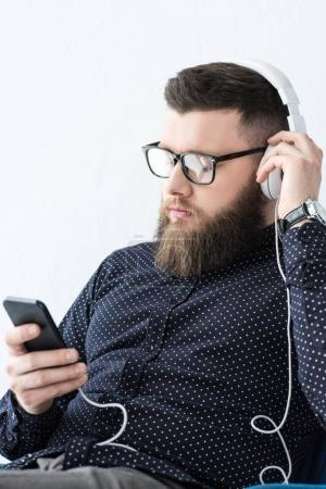 portrait of man with smartphone listening music in headphones