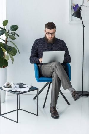 concentrated businessman working on laptop in chair