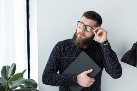 portrait of stylish businessman in eyeglasses with notebook