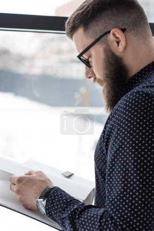 side view of focused businessman reading notebook