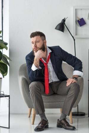 Photo pour Gentil homme d'affaires en costume assis dans le fauteuil - image libre de droit