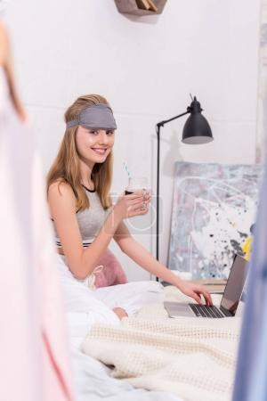happy young woman with beverage in mason jar working with laptop in bed in morning