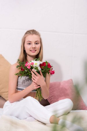 beautiful young woman with beautiful bouquet sitting on bed at home