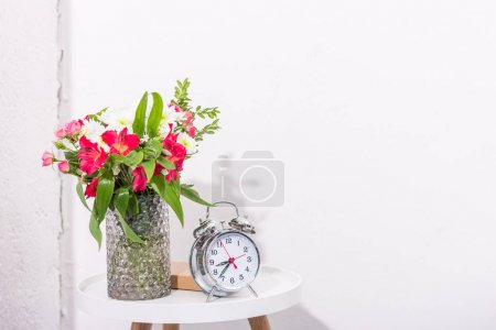vintage alarm clock on table with flowers in vase