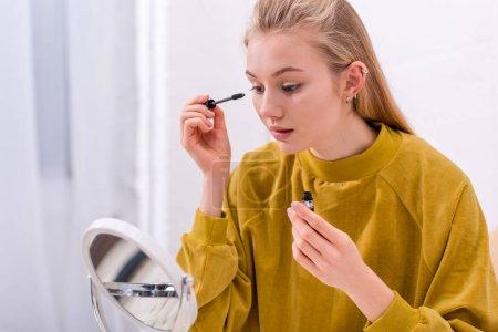young woman applying mascara and looking at mirror