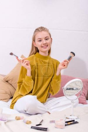 young woman with various makeup supplies sitting on bed at home