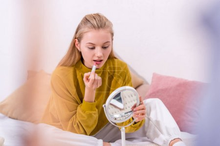 attractive young woman applying lipstick on bed at home
