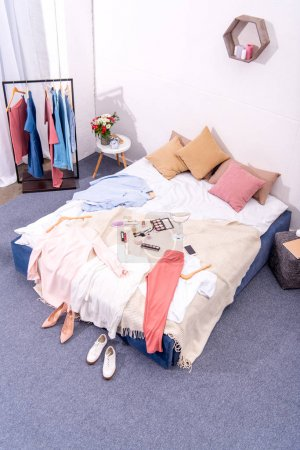 Photo for High angle view of interior of modern bedroom with hanger full of various female clothing and makeup supplies on bed - Royalty Free Image