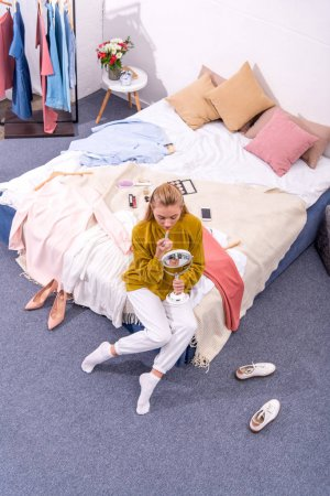 Photo for High angle view of young woman applying lipstick while sitting on bed - Royalty Free Image