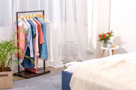 interior of modern bedroom with hanger full of various female clothing