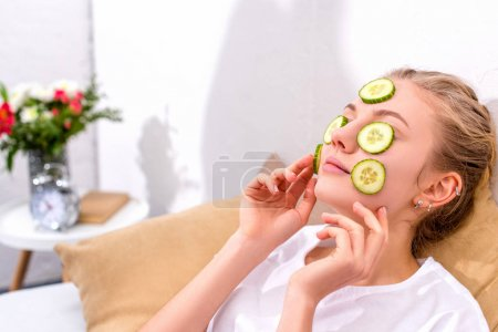 young woman applying cucumber slices on face at home