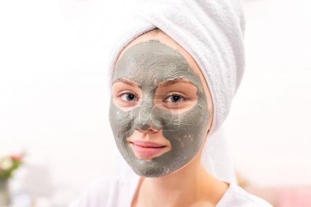 beautiful young woman with cosmetic clay mask at home