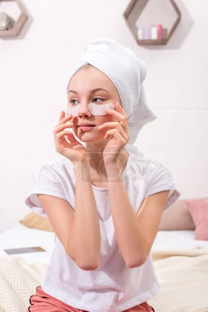 attractive woman spplying cosmetic facial patches at home