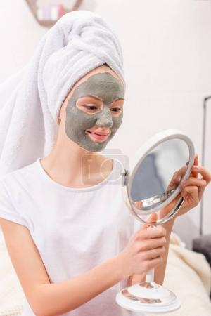 young woman with cosmetic clay mask looking at mirror at home