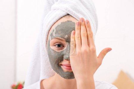 Photo pour Jeune femme avec le masque à l'argile cosmétique couvrant la moitié du visage - image libre de droit