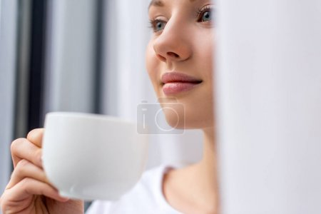 close-up portrait of young woman drinking coffee