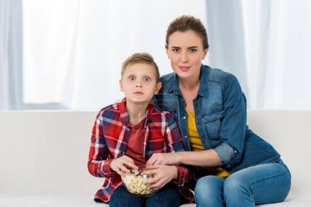 interested mother and son watching movie together with popcorn