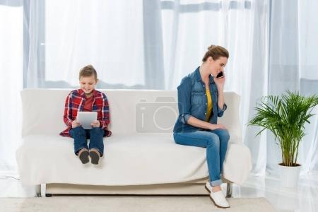happy little son using digital tablet while his mother talking by phone on couch