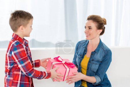 little son presenting mothers day gift to his mother