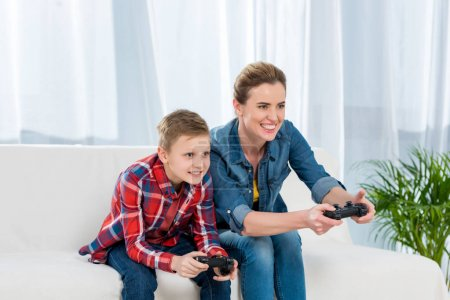 excited mother and son playing video games with gamepads together on couch