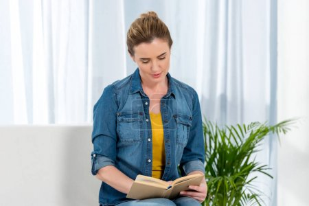 focused adult woman reading book at home