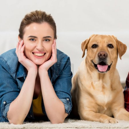 happy woman with her labrador dog lying on floor at home and looking at camera