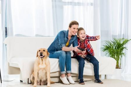 mother and excited son playing video games while their dog sitting on floor