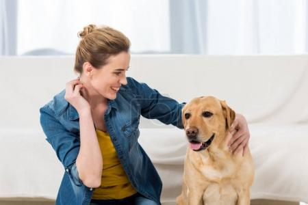 woman petting her labrador dog at home