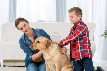 mother and son petting their yellow labrador dog