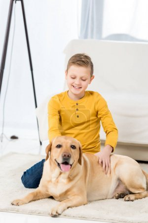 happy little kid petting his dog while sitting on floor