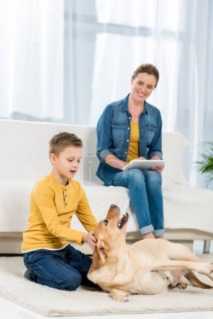 kid petting dog on floor while mother using tablet on couch