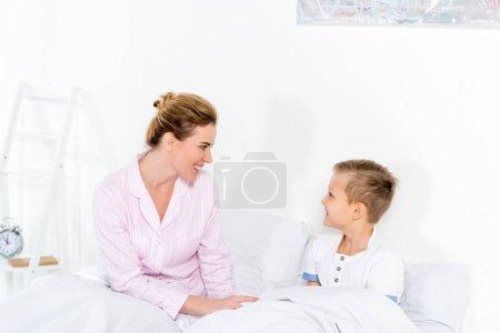 Photo pour Mère et fils, assis dans son lit le matin week-end - image libre de droit